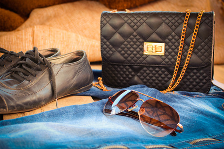 toned image: Sunglasses jeans handbag and old shoes. Toned image.
