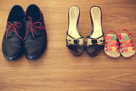 Three pairs of shoes: men women and children. Baby sandals stand next to women39s shoes. concept of the child is friends with his mother. Idea parents divorced child remained with mother. Toned image