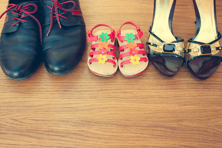 baby shoes: Three pairs of shoes: men women and children. Shoes parents and daughters. Stock Photo