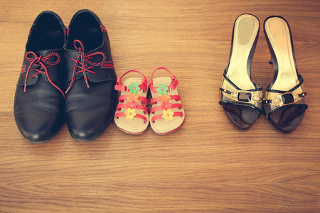 Three pairs of shoes: men women and children. Baby sandals stand next to men shoes. concept of the child is friends with his father. Idea parents divorced child remained with father. Toned image