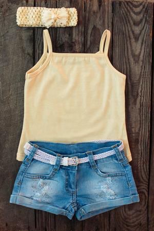 ropa de verano: Camiseta, pantalones cortos de mezclilla, banda para la cabeza en el fondo de madera.