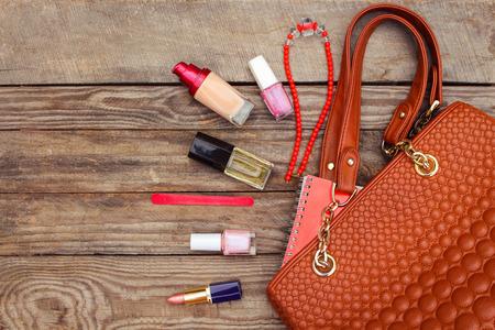 Things from open lady handbag. women's purse on wood background. Toned image. Foto de archivo