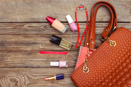 Things from open lady handbag. women's purse on wood background. Toned image. Standard-Bild