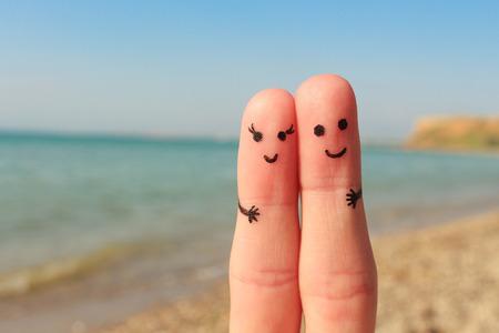 Vinger kunst van een gelukkig paar. Man en vrouw hebben een rust op het strand de zee. Man en vrouw knuffel op de achtergrond zee.