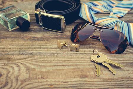 남성 액세서리 : 선글라스, 오래된 나무 배경에 넥타이, 커프스 단추, 끈, 키, 향수. 톤 이미지입니다.