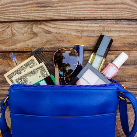 Dingen van open dame handtas. vrouwen portemonnee op hout achtergrond. Cosmetica, geld en accessoires voor vrouwen viel uit de blauwe handtas.