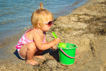 sandcastles: Little girl playing on the beach with pail and shovel. A child age 1 year builds sand pies.
