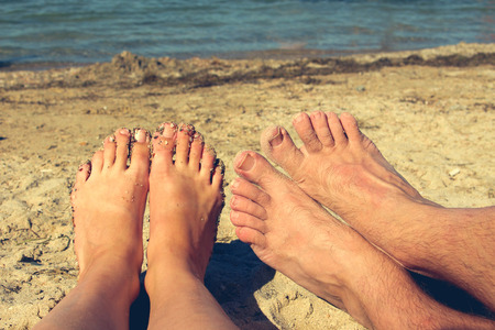 flirt: Female and male feet on the background of blue sea. couple lying and resting on the beach. The concept of a man meets a woman - a holiday romance.