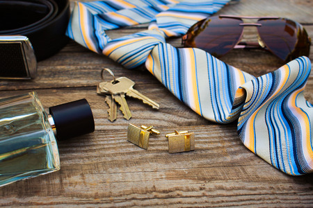 Men accessories: sunglasses, tie, cufflinks, strap, keys, perfume on the old wood background. Toned image.