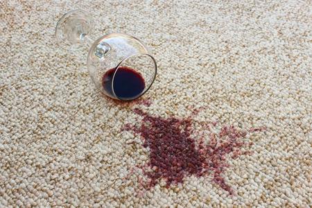 赤ワインのガラスは、カーペットは、カーペットの上にこぼれたワインに落ちた 写真素材