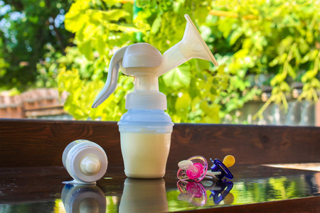 breastfeeding: Breast pump, bottle of milk and pacifiers on the table