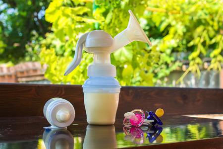 lactancia materna: extractor de leche, botella de leche y chupetes en la mesa