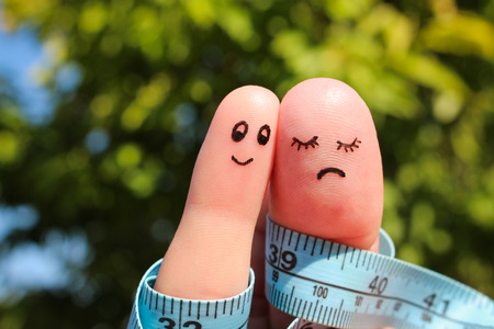fat: Finger art of couple with meter. The concept man is thin, woman is fat.