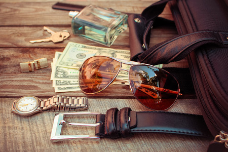 Men accessories: sunglasses, bag, money, wrist watch, cufflinks, comb, strap, keys, perfume on the old wood background. Toned image.