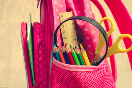 school supplies: Stationery objects. School supplies are in school backpack. Toned image.