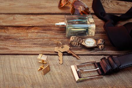 メンズ アクセサリー: サングラス、バッグ、腕時計、カフス、櫛、ストラップ、キー、ネクタイ、香水に古い木材の背景に。トーンのイメージ。