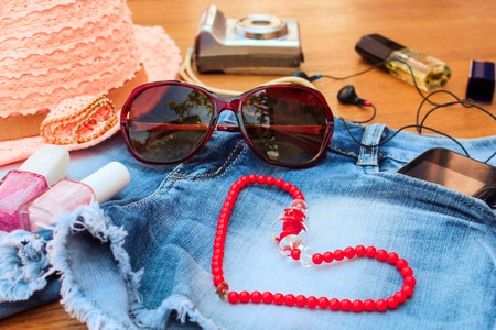 mobile accessories: Summer womens accessories: red sunglasses, beads, denim shorts, mobile phone, headphones, a sun hat, camera, nail polish, open lipstick, perfum Archivio Fotografico