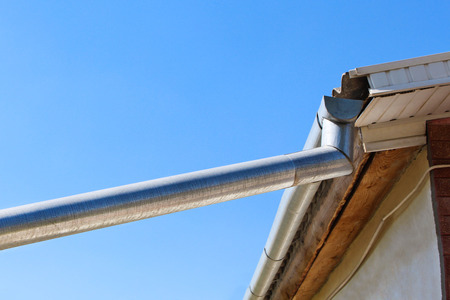 roof: The gutter on the roof on blue sky background