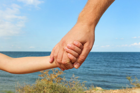 Man holds hand of child on background of sea and sky Concept of love, care, friendship, trust in family.