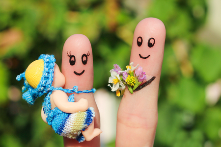 finger: Finger art of a Happy family holding a small child. Concept of husband giving flowers to his wife for birth of child. Stock Photo