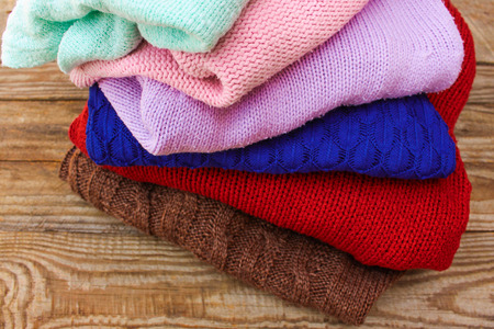 warm things: Pile of colorful warm clothes on wooden background.