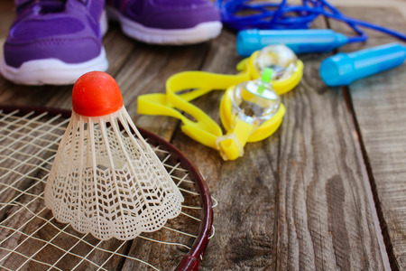 sporting activity: Sports equipment: the birdie is on the racket, skipping rope, swimming goggles and sneakers on wooden background Stock Photo