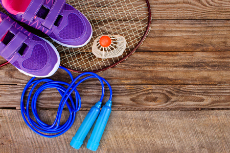 sporting activity: Sports equipment: the birdie is on the racket, skipping rope and sneakers on wooden background