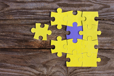 differs: One purple puzzle and many yellow puzzles on wooden background