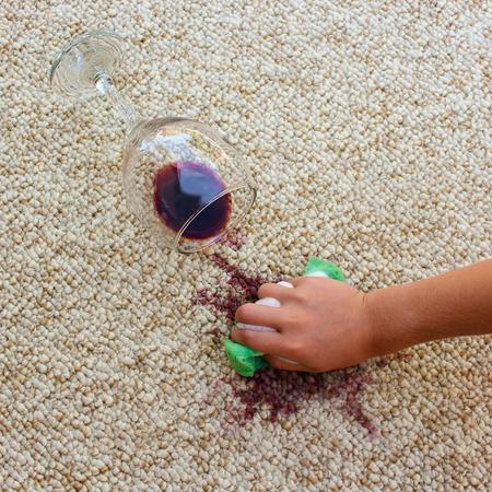 personal de limpieza: vaso de vino tinto cayó en la alfombra, el vino derramado en la alfombra. Mano femenina que limpia la alfombra con una esponja y detergente.