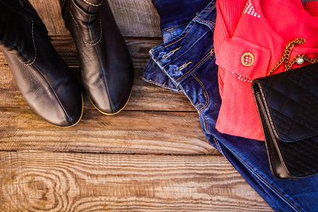 Vrouwen herfst kleding en accessoires: trui, jeans, handtassen, schoenen, parels op houten achtergrond. Getinte afbeelding. Stockfoto