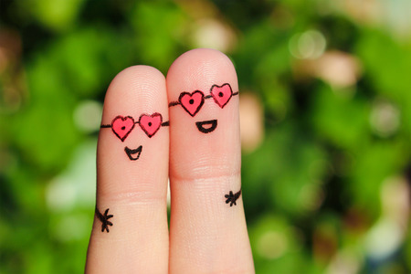 1st: Finger art of a Happy couple. A man and a woman hug in pink glasses in shape of hearts. The concept of love at first sight. Stock Photo