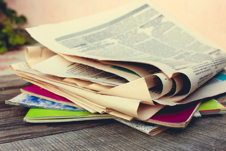 daily newspaper: Newspapers and magazines on old wood background. Toned image.