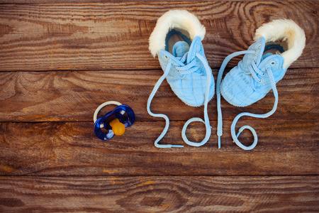 encaje: 2016 a�o escrita cordones de los zapatos para ni�os y un chupete en el fondo de madera vieja. imagen de tonos