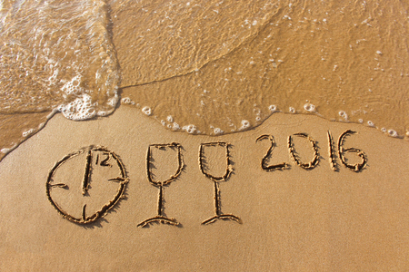 1 2 years: champagne glasses, clock which shows 12 hours, 2016 year written on sandy beach sea