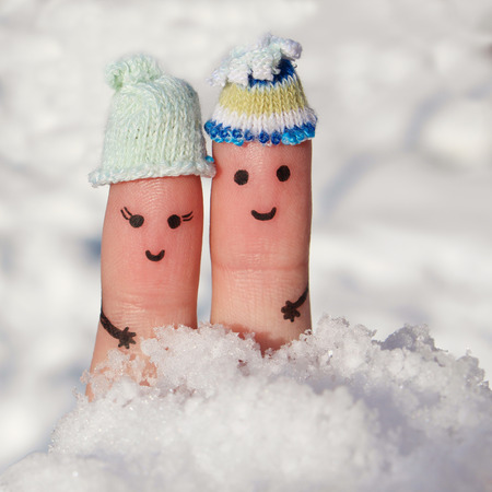 smiley: Finger art of a Happy couple on the background of snow. A man and a woman hug.