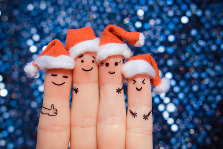 Finger art of friends celebrates Christmas. The concept of a group of people laughing in new year hats. Banco de Imagens