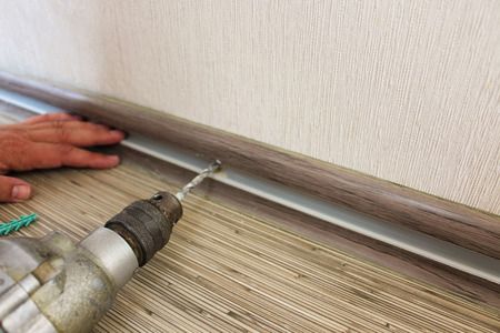 baseboard: The man secures the baseboard to the wall