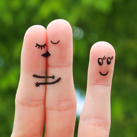 matchmaker: Finger art of a Happy couple. The happy couple kissing and hugging. The other girl looks at them and rejoices. Stock Photo