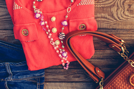 handbag: Womens clothing and accessories: sweater, jeans, handbag, beads on wooden background. Toned image.