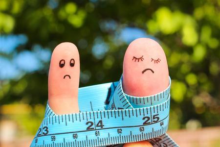 sobre peso: Arte del dedo de la pareja con el metro. El hombre del concepto es delgado, mujer es gordo.
