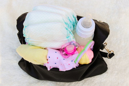 baby stuff: Womens handbag with items to care for the child