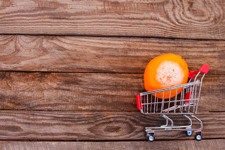 mildewed: Shopping cart with rotten orange on the old wood background. Mold on food. The concept of selling spoiled food. Toned image.