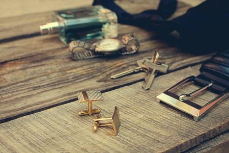 Männer Zubehör: Armbanduhr, Manschettenknöpfe, Gürtel, Schlüssel, Krawatte, Parfüm auf dem alten Holz Hintergrund. Getönten Bild.
