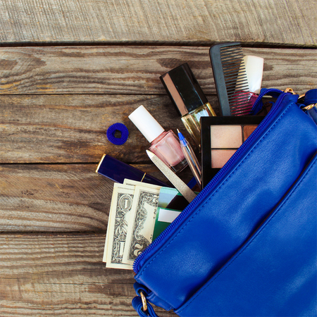 handbag: Things from open lady handbag. womens purse on wood background. Cosmetics, money and womens accessories fell out of the blue handbag.