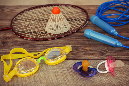 birdie: Pacifier and sports equipment: the birdie is on the racket, skipping rope, swimming goggles on wooden background. Concept of sports to be engaged with early childhood. Toned image.