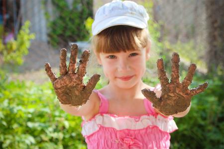 manos sucias: La muchacha muestra las manos sucias.