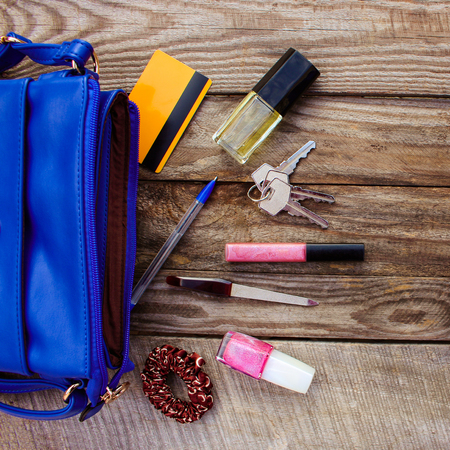 Blue women's purse and women's accessories. Things from open lady hand bag.
