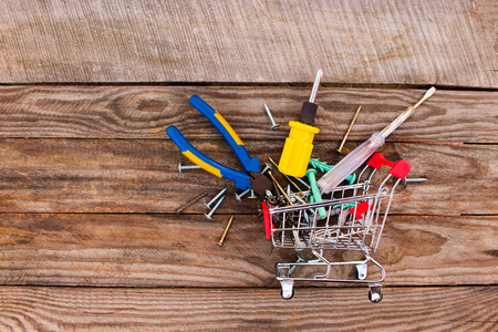 purchases: Shopping cart with construction tools on the old wood background. Toned image.