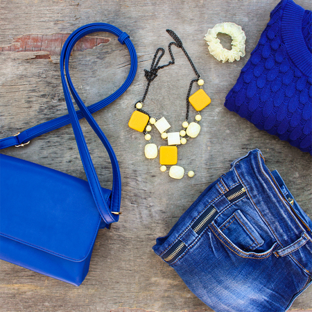 warm things: Womens autumn clothing and accessories: blue sweater, jeans, handbag, beads on wooden background. Stock Photo