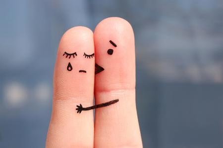 Vinger kunst van ontevreden paar. Vrouw huilt, man stelt haar gerust. Hij kust en koestert haar. Stockfoto